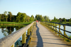 Wooden footbridge railings lake blur people walk Royalty Free Stock Photos