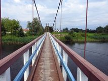 Wooden footbridge by river, Lithuania Royalty Free Stock Image