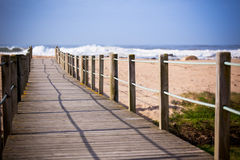 Wooden footpath through dunes at the ocean beach Royalty Free Stock Photo