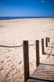 Wooden footpath through dunes at the ocean beach in Portugal Stock Photos