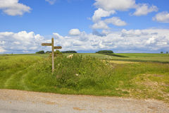 Wooden footpath sign. A wooden footpath sign in scenic summer countryside in the yorkshire wolds england with a blue cloudy sky Royalty Free Stock Image