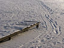 Wooden footway and footsteps on frozen pond royalty free stock photos