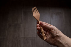 Wooden fork in the hand of women on dark wooden background Royalty Free Stock Image