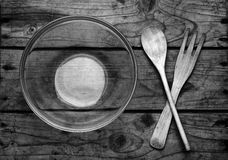 Wooden fork and spoon. Fork, spoon and glass plate on wooden surface Stock Image