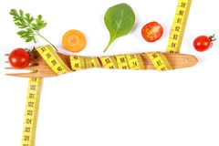 Wooden fork wrapped centimeter and fresh vegetables, concept of lose weight and healthy nutrition. Wooden fork wrapped tape measure and fresh ripe vegetables on stock photos