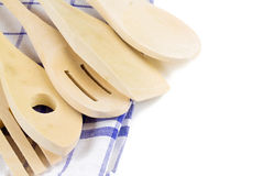 Wooden forks, spoons and spatulas on kitchen towel on w Stock Photos