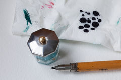 Wooden fountain pen nib with inkwell, blotter, napkin. White paper textured background. Stock Image