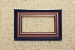 Wooden frame on beige paper background Stock Images