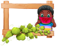 A wooden frame with a boy eating watermelon Royalty Free Stock Photos