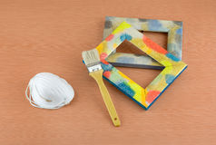 Wooden frame, brush and respirator on table Stock Photo