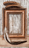 Wooden frame, burlap ribbon and feathers on the old wood Stock Photos