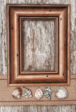 Wooden frame, burlap ribbon and seashells on the old wood Stock Photography