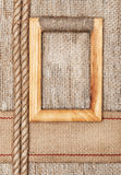Wooden frame on the burlap with sacking ribbon and rope. Wooden frame on the burlap textile background with sacking ribbon and rope Stock Photos