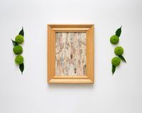 Wooden frame with collage of birch bark. Wooden frame with collage of birch bark with decoration of chrysanthemum flowers and ficus leaves on white background Royalty Free Stock Photography
