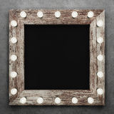 Wooden frame on concrete background illuminated by light bulbs stock illustration