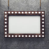 Wooden frame on concrete background illuminated by light bulbs royalty free illustration