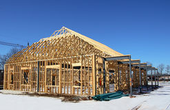 Wooden Frame Construction. Home construction wooden framing after white snow falls under blue sky stock photos