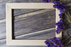 Wooden frame with dried blue flower decoration on the wooden table Royalty Free Stock Photography