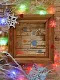 A wooden frame with empty space on a stone textural background is decorated with festive illumination and Christmas decoration. Congratulations on seasonal stock photography