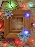 A wooden frame with empty space on a stone textural background is decorated with festive illumination and Christmas decoration. Congratulations on seasonal royalty free stock images