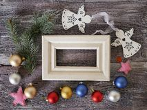 Wooden frame with empty space, on a wooden rough texture background, seasonal festive decor, balls, hearts, stars, top view royalty free stock images