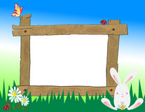 Wooden Frame in Field. A wooden frame in a field with butterfly, ladybugs, daisies and rabbit around it on a bright day. Copy space in frame Royalty Free Stock Photos