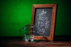 Wooden frame with happy st patricks day inscription and empty beer glass. On table stock image