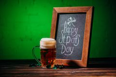 Wooden frame with happy st patricks day inscription and glass of beer. On table royalty free stock photography