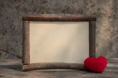 Vintage style wooden frame with heart on the wooden table stock photography