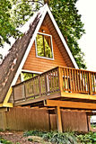 Wooden A-Frame House / Deck. A wooden A-frame house with deck area on front stock photos