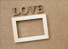 Wooden frame and love wooden text. On corkboard background, valentine concept Stock Photos