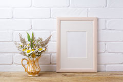 Wooden frame mockup with chamomile and grass in golden pitcher. Wooden frame mockup with white field chamomile and grass in golden pitcher vase. Empty frame mock Royalty Free Stock Image