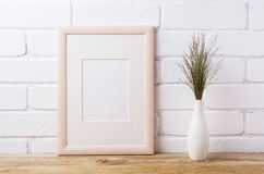 Wooden frame mockup with dark grass in elegant vase Royalty Free Stock Photography