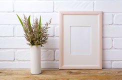 Wooden frame mockup with grass and green leaves in cylinder vase Royalty Free Stock Images