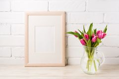 Wooden frame mockup with magenta pink tulips in glass pitcher ja. Wooden frame mockup with bright magenta pink tulip bouquet in the glass pitcher jar. Empty Royalty Free Stock Photos