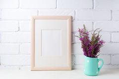 Wooden frame mockup with maroon purple flowers in mint pitcher. Wooden frame mockup with maroon purple field flowers in polka dot mint green pitcher vase. Empty Stock Image