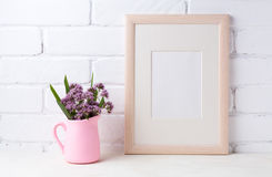 Wooden frame mockup with purple flowers in pink pitcher. Wooden frame mockup with purple field flowers in pink rustic pitcher vase. Empty frame mock up for Stock Photos
