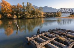 Wooden frame of the old pier in the fall in the bay of the Columbia River. Aun landscape with an old abandoned rotten wooden pier in the bay of the Columbia stock photography