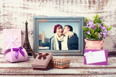 Wooden Frame with picture of young couple and romantic accessori. Es with gift boxes on wooden background Stock Images