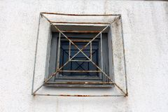 Wooden frame window with rusted rectangle bars. Wooden frame rectangle window with partially rusted metal bars mounted on wall outside Royalty Free Stock Images