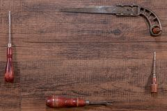 Wooden frame represented by Old and antique tools. Set of old, antique Wooden Handle Tools and an old metal saw shaped to a frame with text placement royalty free stock photography
