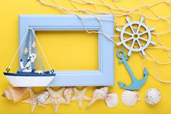 Wooden frame with seashells. On yellow background Royalty Free Stock Photo