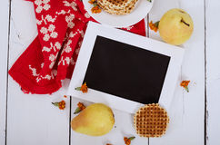 Wooden frame on the table with pears, waffles and red cloth. Horizontal view Royalty Free Stock Images