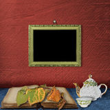 The wooden frame on the wall and  teapot. With  cup of tea on the table Stock Photography