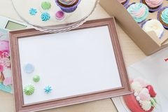 Wooden frame with white sheet around meringue and cupcake with multi-colored cream, kitchen scale, magazine stock image