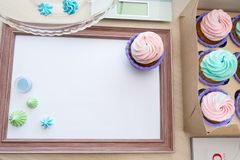 Wooden frame with white sheet around meringue and cupcake with multi-colored cream, kitchen scale, magazine stock photography