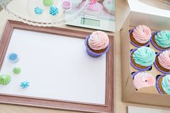 Wooden frame with white sheet around meringue and cupcake with multi-colored cream, kitchen scale, magazine stock images