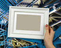 Wooden frame in woman hands. Abstract Metal construction background Royalty Free Stock Photography