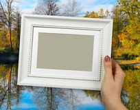 Wooden frame in woman hands on the background autumn colorful foliage over lake Stock Images