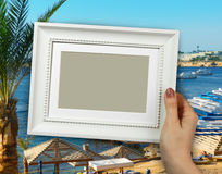 Wooden frame in woman hands on the background Beach Stock Images